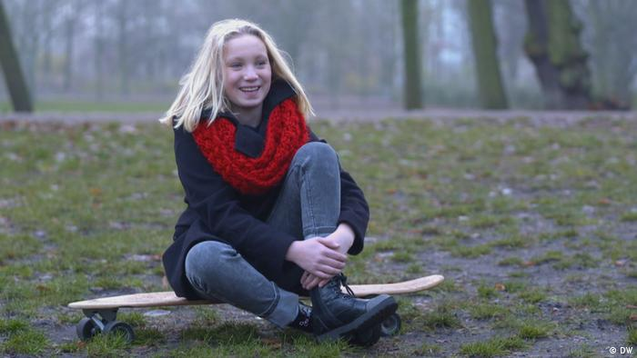 Helena Zengel sits in the forest on a skateboard, smiling.