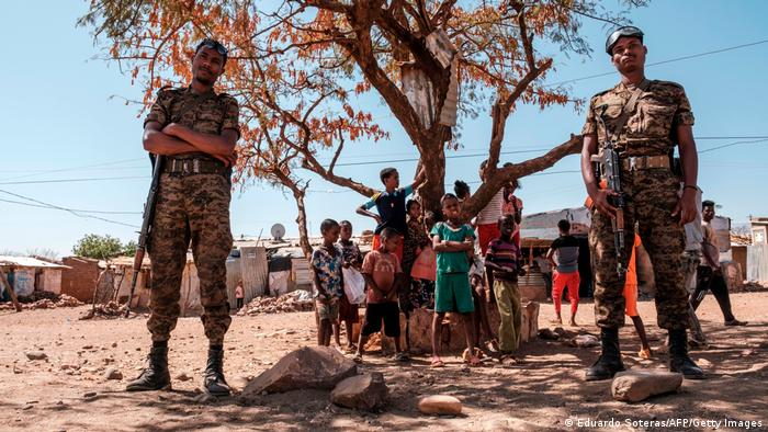 Ethiopian Army soldiers stand as a children stand behind them at Mai Aini Refugee camp,