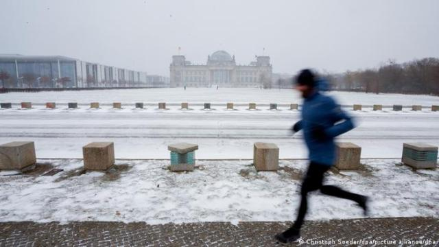 A jogger runs close to the Reichstag building in Berlin