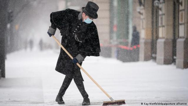 Hotel worker sweeping snow in Berlin