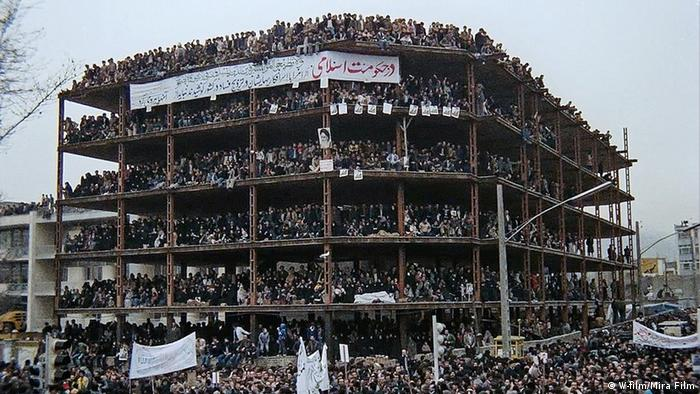 Filmstill from 'The Naked King' showing hundreds upon hundreds of people crowded onto a half-constructed building, holding banners.