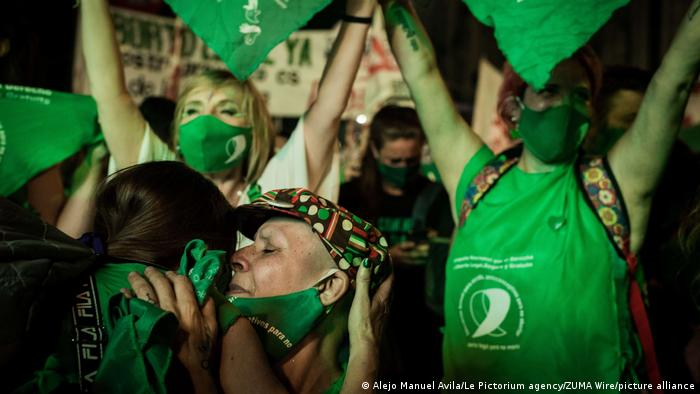 Women wearing green shirts and masks celebrating in Buenos Aires, Argentina.