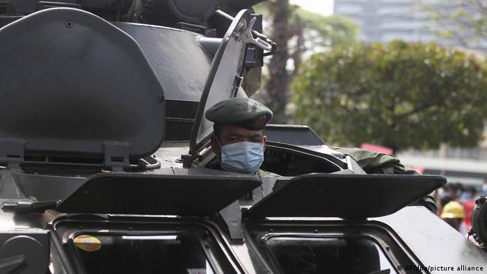 A soldier looks out of a hatch of an armored personnel carrier