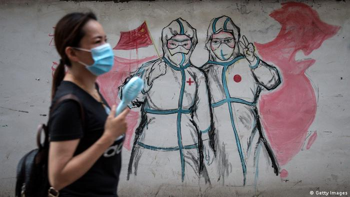 A resident wears a mask while passing the graffiti of Nurses fight against new coronavirus in Wuhan