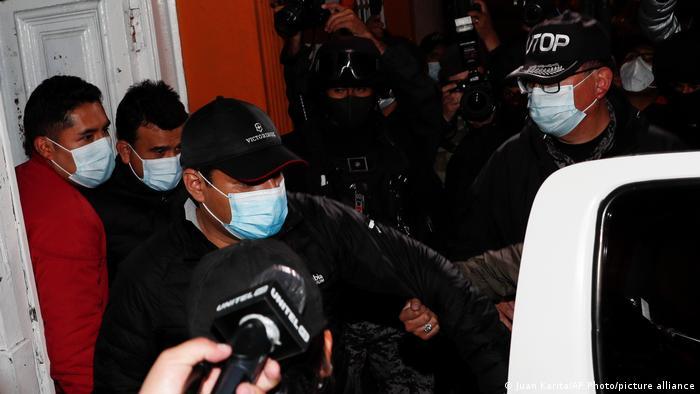 El exministro de Justicia, Álvaro Coímbra (en el centro) y el exministro de Energía, Rodrigo Guzmán (de negro y detrás de Coimbra) son escortados por la policía en La Paz (12.03.2021)