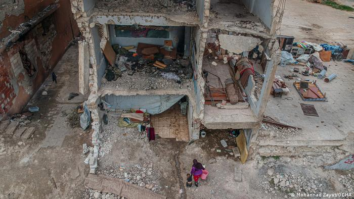Mohannad Zayat shows a woman and child taking refuge in a destroyed school