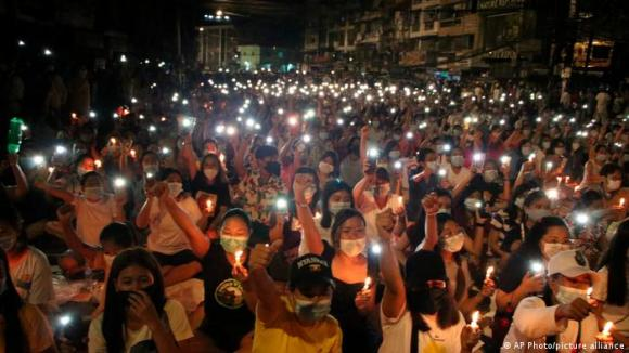 Protesters holding up cell phones with LED lights on in Yangon