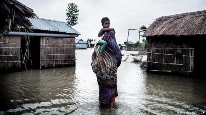 A mother is trying to cross floodwater with her child.