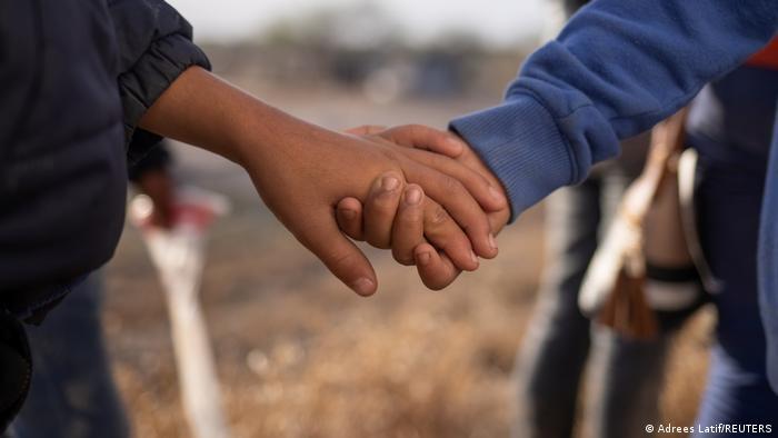 Foto de dos niñas migrantes que se toman de la mano mientras cruzan la frontera a Estados Unidos