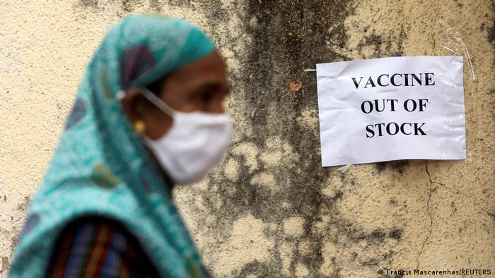 A woman walks past a sign that says Vaccines Out of Stock