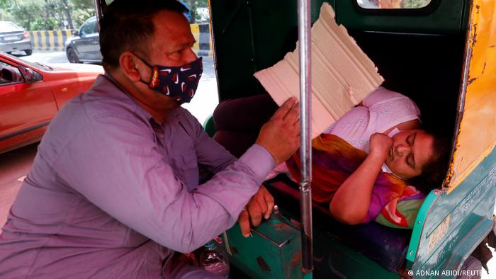 A woman sick with COVID-19 lies in a car in Ghaziabad, India.