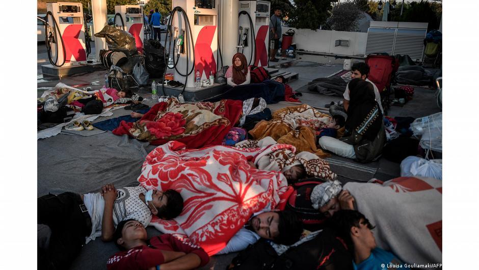 People sleeping on ground at gas station. Photo:|Louisa Gouliamaki, Lesbos, Greece