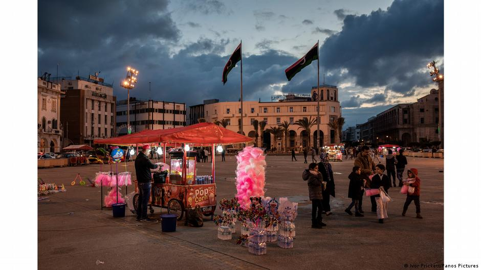 Candy stall lit up at twilight in the middle of a square. Photo:Ivor Prickett, Libya