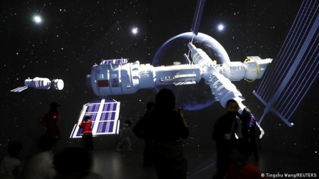 Visitors stand near a giant screen displaying the images of the Tianhe space station