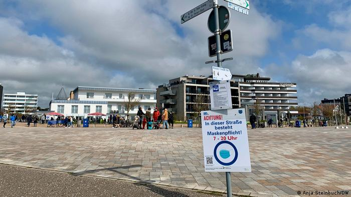 A sea promenade sign reminding people to wear a mask