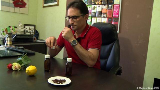 Homem sentado à mesa treinando o olfato com rosas, mamão, perfumes