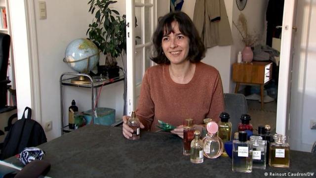Mulher sentada a mesa cheia de frascos de perfume