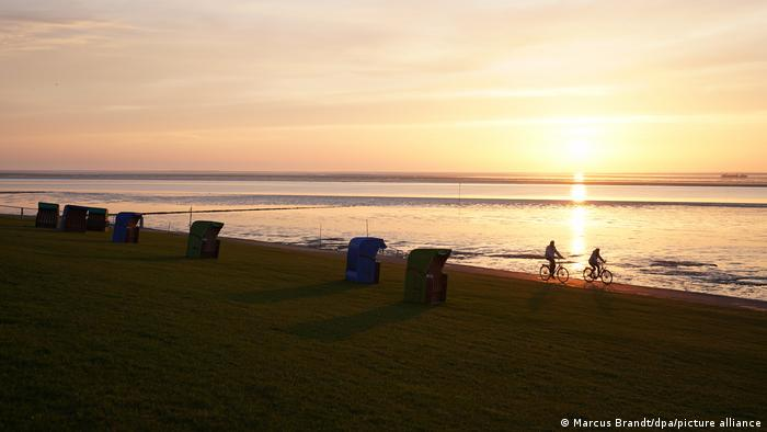 Cyclists riding along the beach front at sundown at the North Sea, Germany
