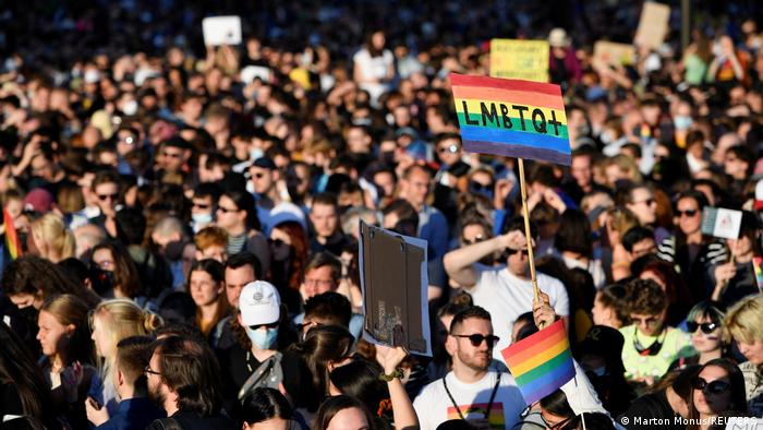 Crowd of protesters, some with rainbow LGBTQ placards
