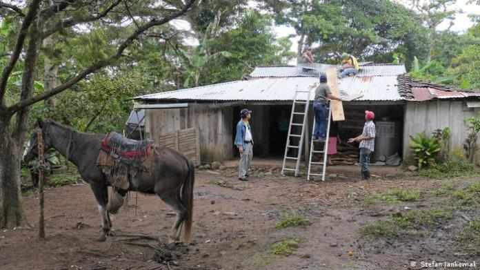 A horse stands in front of a farmer's house in Miraflores in Nicaragua as electricians sets up solar panels on the roof.