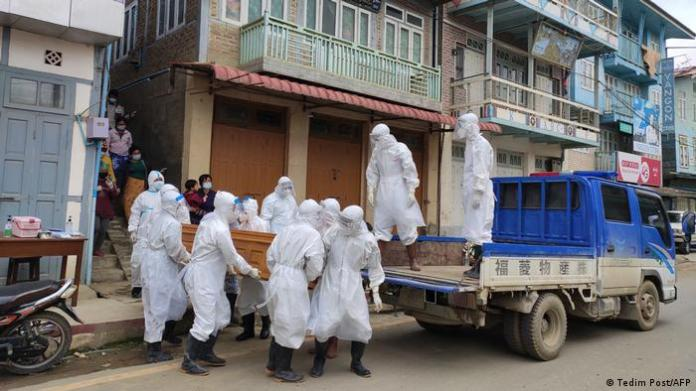 The photo shows health workers carrying a coffin bearing the remains of a COVID victim who died at home in Tedim, western Chin state, Myanmar