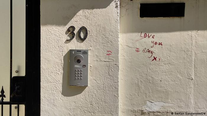 Close-up of the door to Amy Winehouse' home with lipstick impressions on the wall and red handwriting, saying Love you, Amy