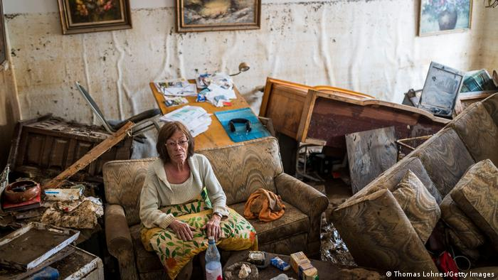 A woman sitting in a destroyed room