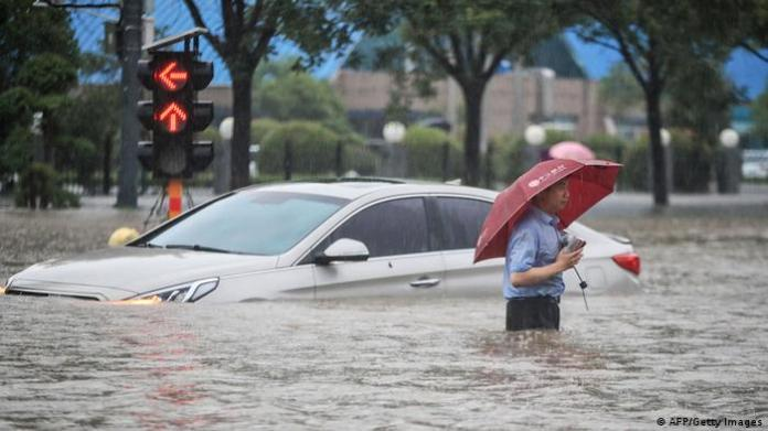 A man wading past a submerged car along a flooded street following heavy rains in Zhengzhou in China's central Henan province