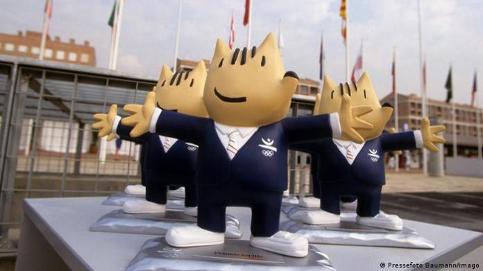 Large figures of a smiling creature wearing a blue suit , outdoors on a platform, building with flags in the background