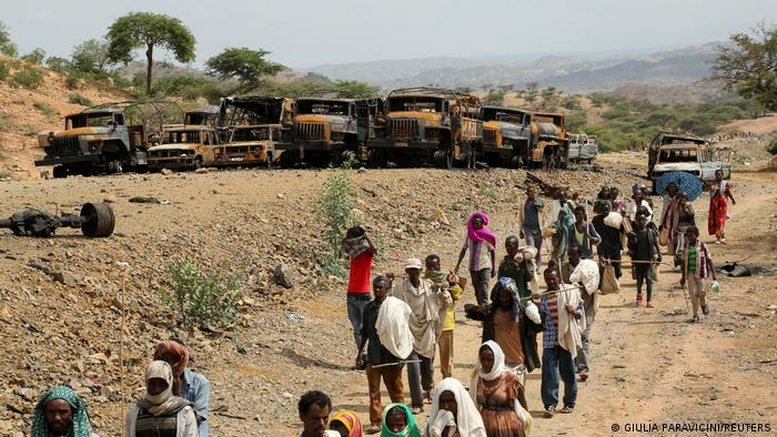 Villagers return from a market to Yechila town in south central Tigray walking past scores of burned vehicles, in Tigray, Ethiopia, July 10, 2021