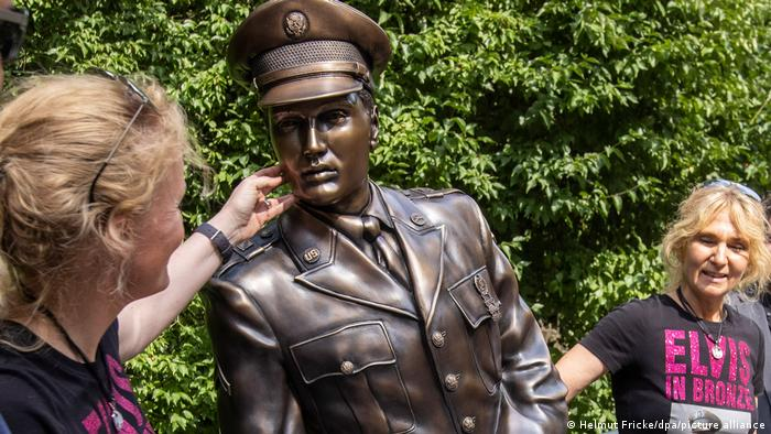 Angela Storm and Meike Berger stand next to a bronze statue of Elvis in Bad Nauheim, Germany