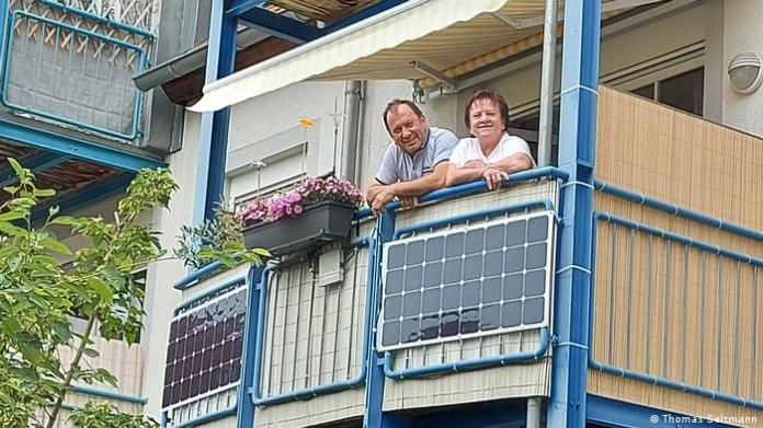A couple looks over a balcony where solar panels have been installed