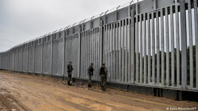 Three men stand in front of a tall metal fence