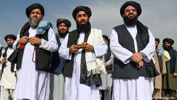 Taliban spokesman Zabihullah Mujahid (C) speaks to the media at the airport in Kabul flanked with two other members of the Taliban