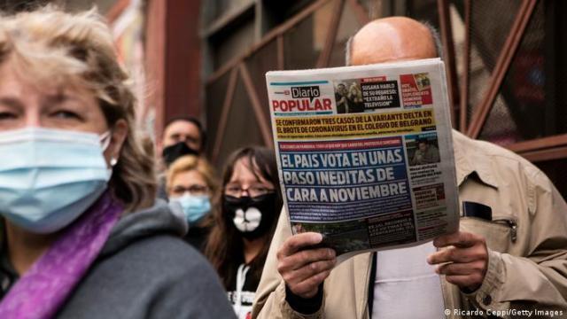 Primarias legislativas en Buenos Aires: un hombre lee un periódico sobre los comicios.