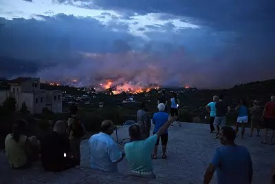 People watch a wildfire in the town of Rafina, near Athens, on July 23, 2018.