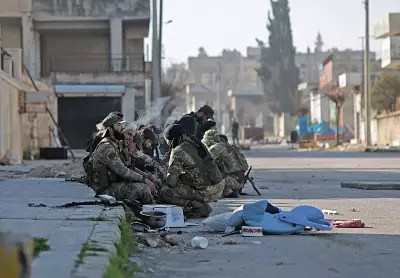 Turkey-backed Syrian fighters rest in the town of Saraqib in Syria\'s Idlib province on Thursday.