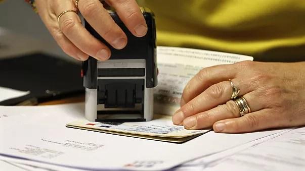 Une employée tamponne un visa