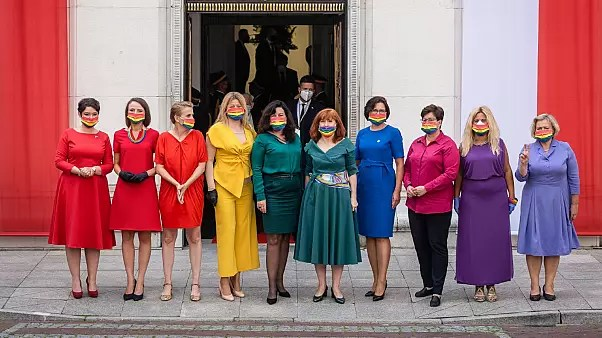 Left wing parliamentarians dressed in the colours of the rainbow pose in front of the Polish Parliament (Sejm)
