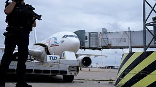 A gendarme guards a government plane carrying people from Kabul at the Roissy Charles Gaulle airport, north of Paris.