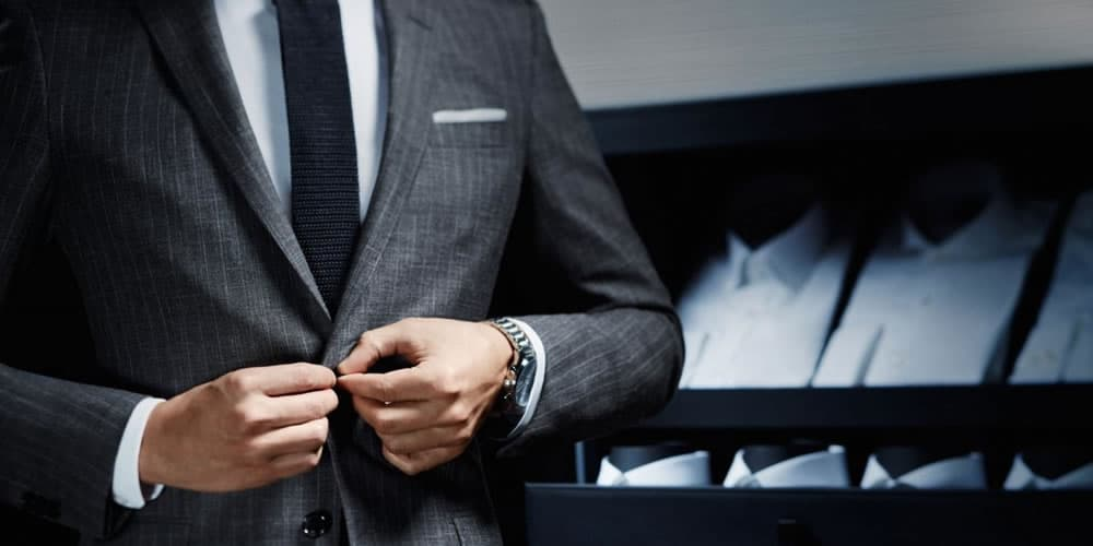 Homme vêtu d'un costume gris avec une cravate bleu marine