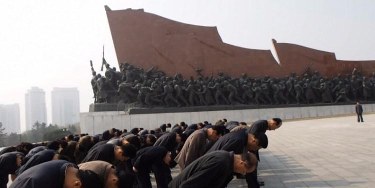 Grupo de hombres en Corea del Norte rindiendo homenaje a los padres de la patria
