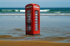 Iconic UK Red traditional phone box on a beach