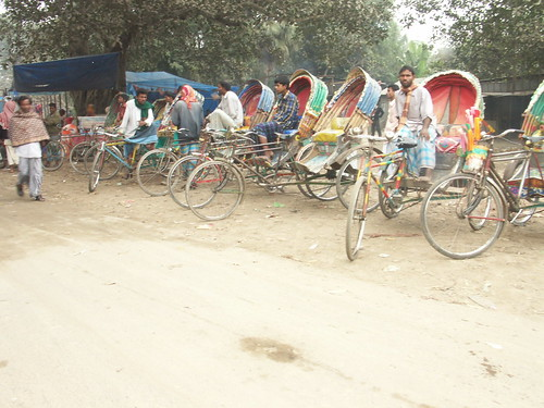Many rickshaws in this village market are financed by the wife, who happens to be a grameen member