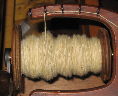 Ecru wool on the bobin of a spinning wheel - Laine écrue sur la bobine d'un rouet