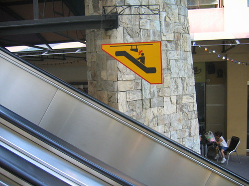 self-referential warning sign over escalator
