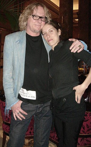Mike Mills vistiendo una remera de 134 junto a Diana Muia