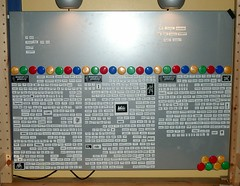 Image of a desk with a metal back board. small tiles of words are magnetically attached to the back board.