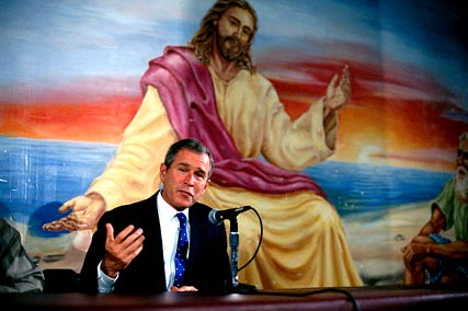 George W Bush speaks in front of a mural while on campaign trail in 2000