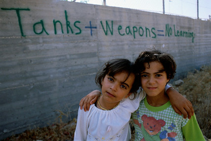Palestinian children stand along Israel's wall in the West Bank